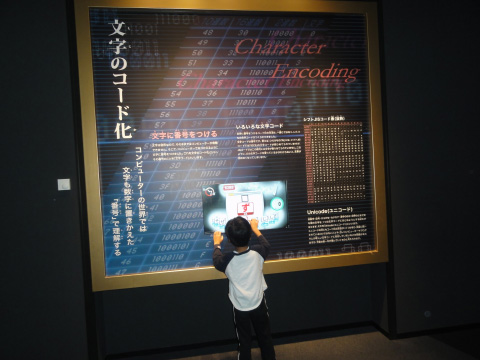 A little child playing an encodings game in front of a large poster about encodings.